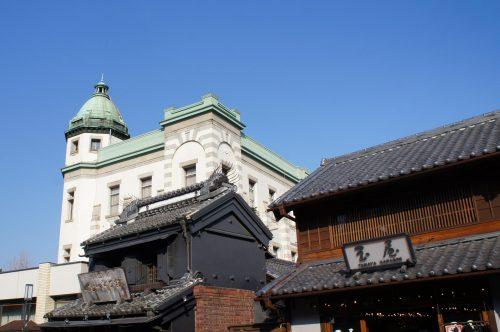 """Auf diesem Foto, hinter den Gebäuden von Kura no Machi (die """"Kura Straße"""" mit den alten Lagerhäusern, die für Kawagoe berühmt sind), sehen wir eine Bank im westlichen Stil aus dem Jahr 1918."""