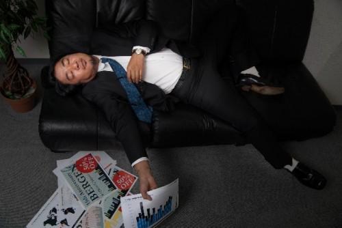 Hombre de negocios japonés, cansado por haber trabajado mucho.