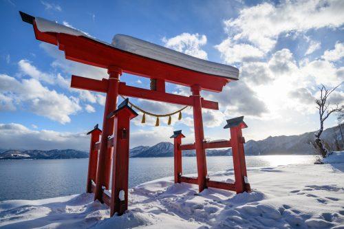 El torii Gozanoishi a la orilla del lago Tazawa, Akita, región de Tohoku, Japón.