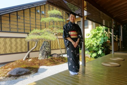 A staff member in kimono greets guests at Ryokan Shinsen in Takachiho.