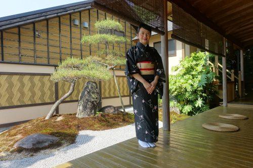 Une employée vêtue d'un kimono, devant le jardin japonais du ryokan Shinsen de Takachiho