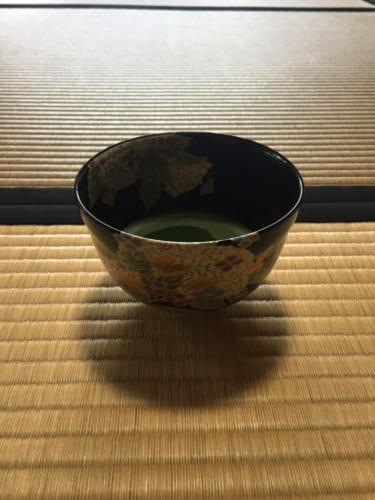 Bol de thé vert matcha posé sur le sol en tatami dans une maison de thé à Saiki