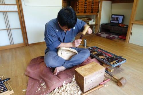 Le maître artisan en pleine sculpture d'un masque de kagura dans son studio