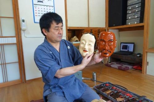 Le maître artisan montre des masques de kagura qu'il vient de réaliser