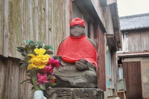 Jizo devant lequel est disposé un arrangement floral dans les ruelles d'Ojika