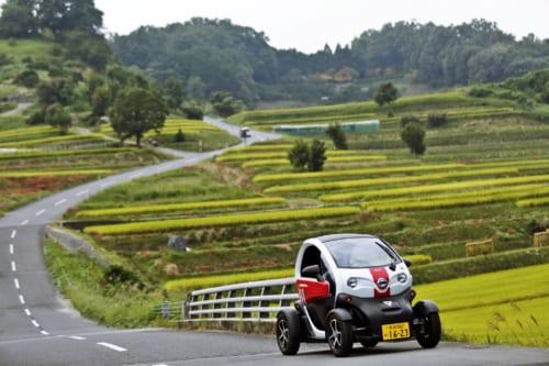 Une voiture électrique Michimo, sur la route au milieu des rizières d'Asuka