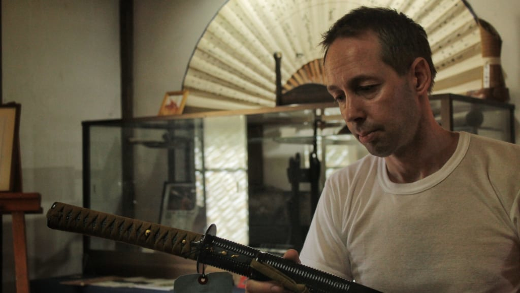 Hans Koga montrant un katana dans son atelier à Higo Minkamura