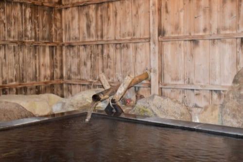 Le bain commun du Minshuku Yamanosato, palissades de bois et bassin entouré de pierres