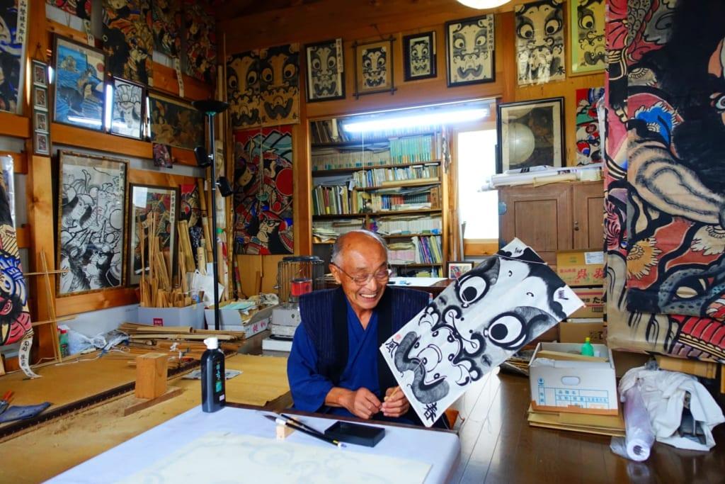 M. Ono souriant, pose avec son cerf-volant terminé dans son atelier à Yuzawa, préfecture d'Akita