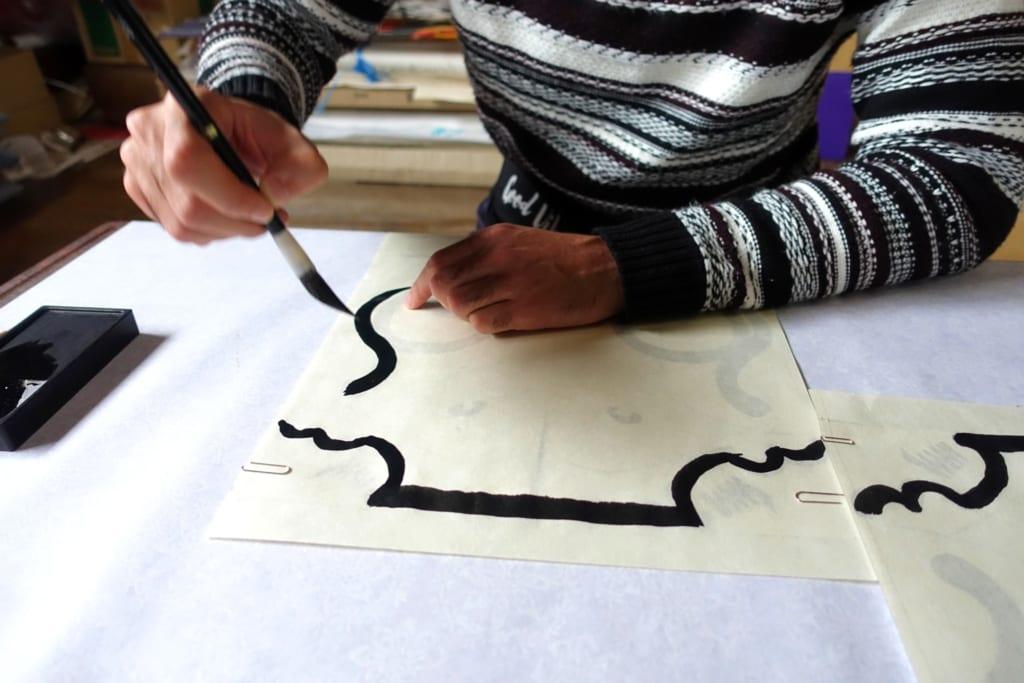 Les contours des motifs du cerf-volant traditionel tracés à l'encre sumi