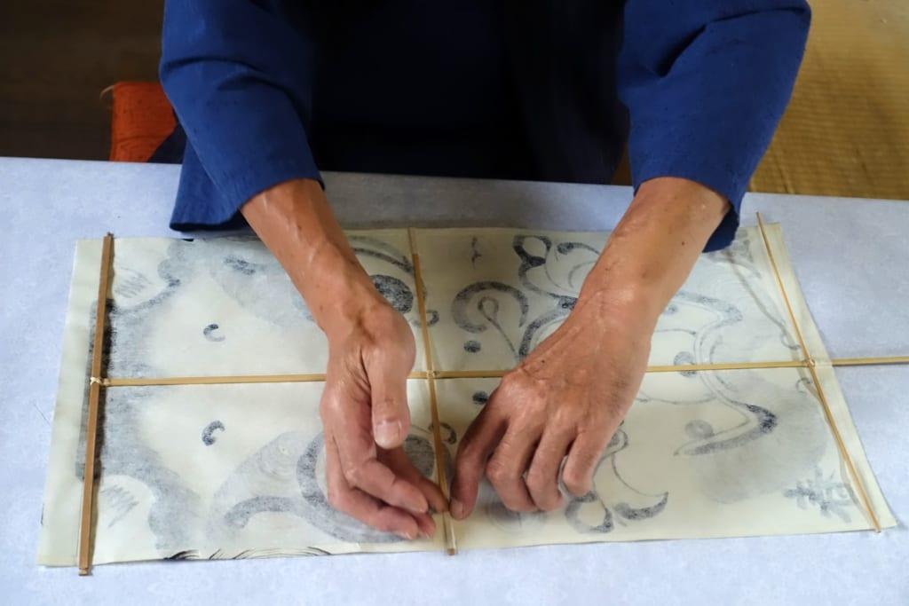 L'artisan place minutieusement l'armature en bambou du cerf-volant sur le papier peint à la main