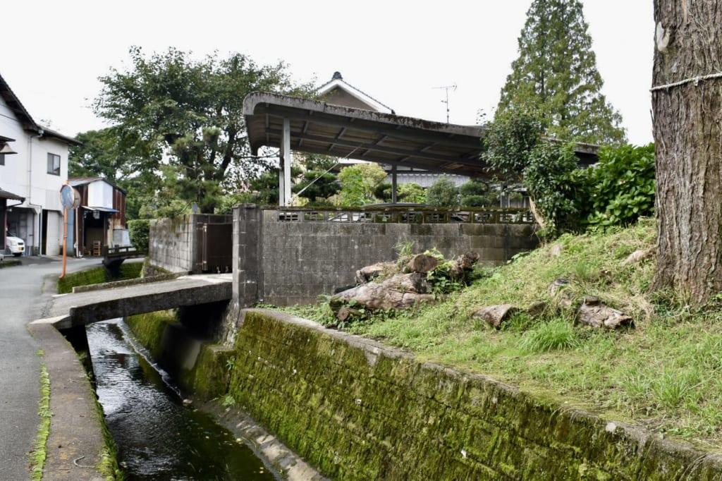 Ruelle dans le quartier près du sanctuaire d'Aso : un pont de pierre permet d'entrer dans une propriété
