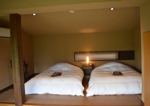 Deux lits à l'occidentale, préparés dans la chambre à la décoration japonaise sobre