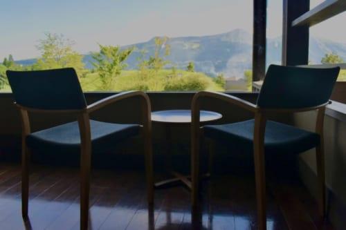 Deux chaises et une petite table, positionnées pour profiter de la vue sur la caldera du mont Aso