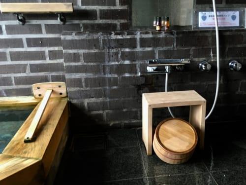 L'onsen privatif et son coin douche, équipé d'accessoires en bois clair