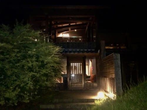 Bâtiment du ryokan Konomama vu de nuit, les lumières sont allumées à l'intérieur