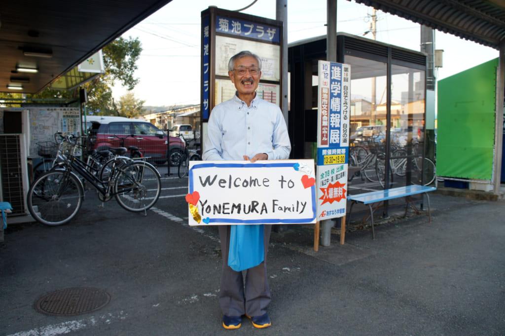 "M. Yonemura, deant la gare routière avec une pancarte ""welcome to Yonemura family"""