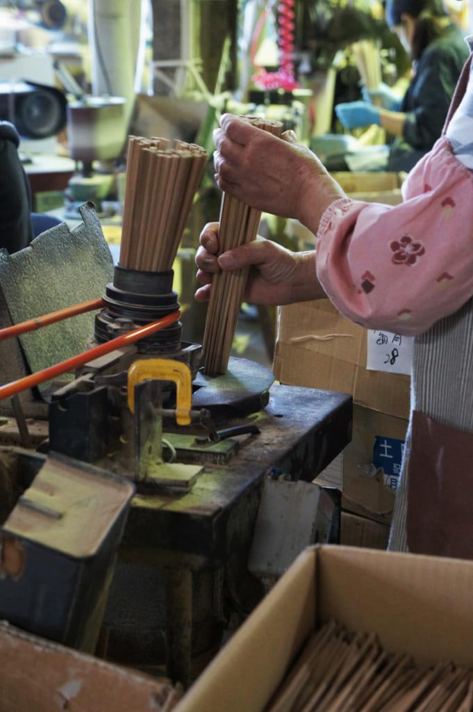 Mains d'une ouvrière qui travaille sur des finitions de baguettes à l'usine de Yamachiku