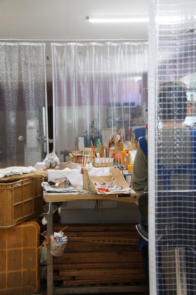 Ouvrière travaillant à la peinture des baguettes dans l'atelier de Yamachiku