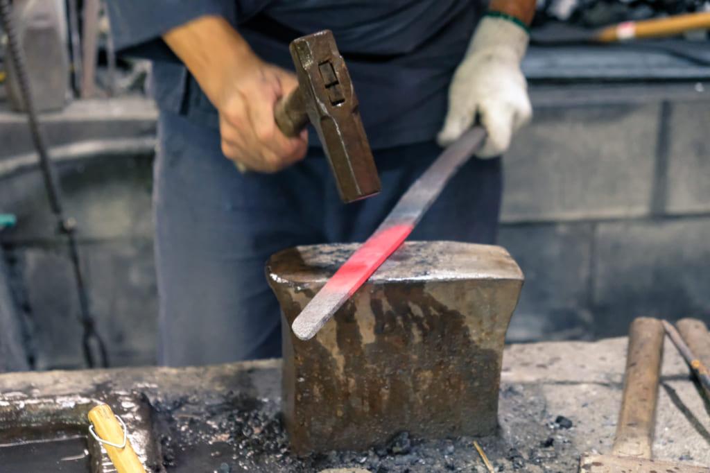 M. Matsunaga donne sa forme au katana en frappant sur le fer à l'aide d'un marteau
