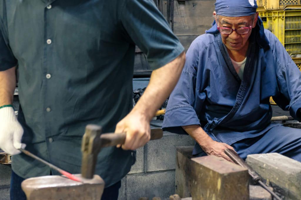 M. Matsunaga observe attentivement mon collègue s'essayant à la forge d'un katana