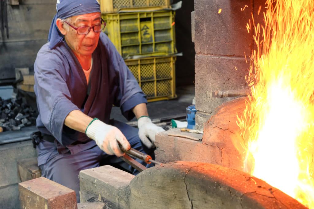 Les étincelles jaillissent de la forge que m. Matsunaga attise