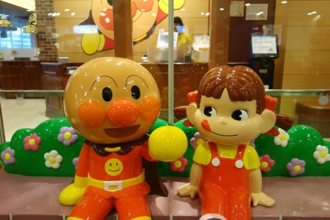 anpanman sitting with the mascot of fujiya cakes