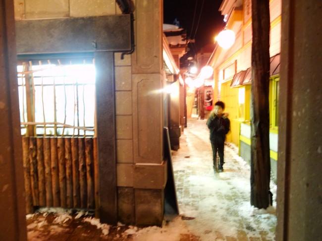 Alley with a little snow and person walking through in Denuki of Otaru, Hokkaido.