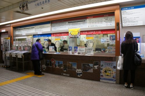 Seibu Shinjuku Station Ticket Desk: Tickets for the Red Arrow train are at the red desk.