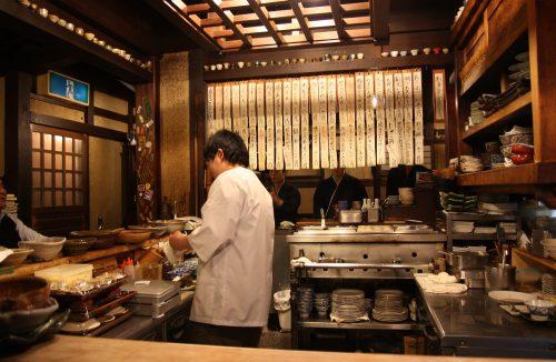 A chef prepares dishes at Mingeichaya, an izakaya restaurant in Kurashiki, Okayama.