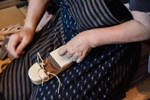 Maestro artesano introduciendo el hanao en el zapato geta.