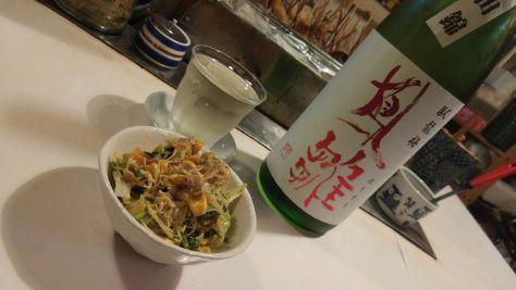 Suivez le jouren : bouteille d'alcool et petit bol dans une izakaya au Japon.