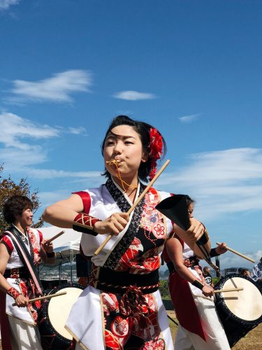 A woman plays the whistle to accompany the percussion