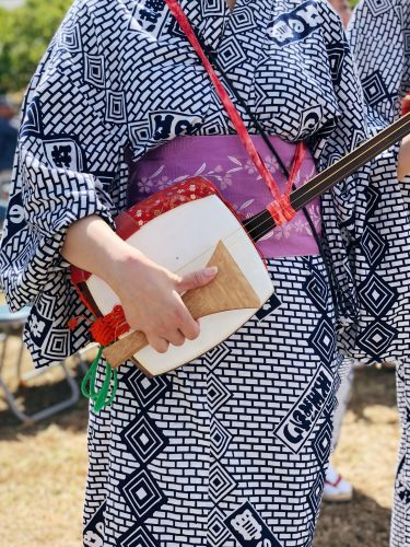 a woman plays a traditional japanese musical instrument