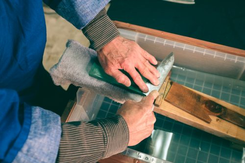 Artisan mending a blade on a water stone, Wada shop, Sakai, Osaka, Japan