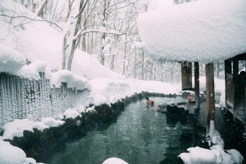 Bain chaud mixte en plein air entouré par la neige à Nyuto Onsen, Akita, Japon