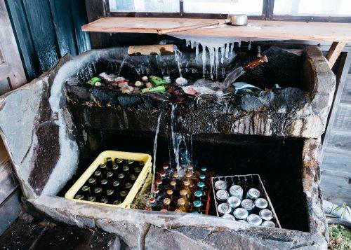 Les boissons du ryokan Tsurunoyu conservées dans une fontaine à Nyuto Onsen, Akita, Japon