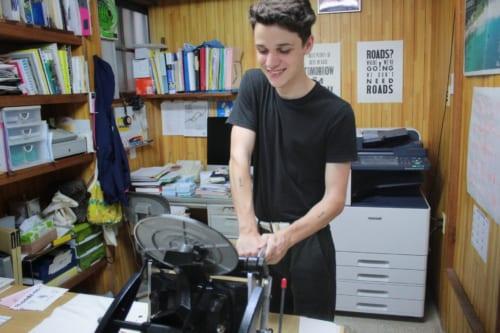 Luca imprimant sa carte postale sur la presse de l'imprimerie Ojikappan