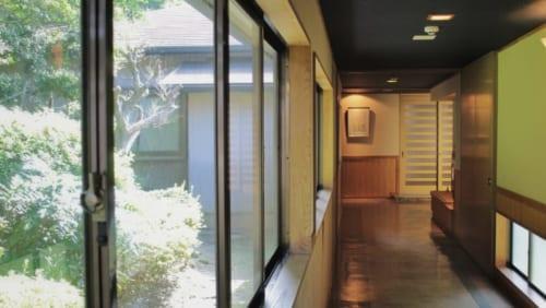 Un couloir du ryokan Satsuki Bessou de Tamana, dont les grandes baies vitrées donnent sur un jardin
