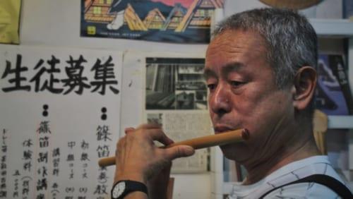 Le propriétaire de Yama Biko jouant de l'une de ses flûtes