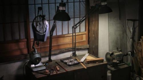 Table de mesure, éclairée par des lampes dans l'obscurité de l'atelier d'Hans Koga