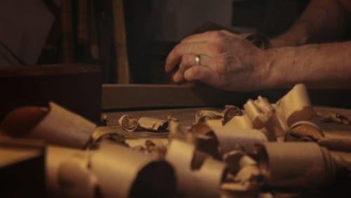 Les mains d'Hans Koga au travail, derrière un premier plan de copeaux de bois