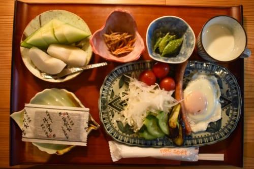 Petit déjeuner varié : fruits, légumes, œufs, etc. dans de la vaisselle japonaise