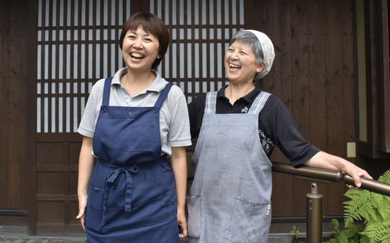 Yuri et sa mère, tout sourire devant leur maison d'hôtes à Ubuyama