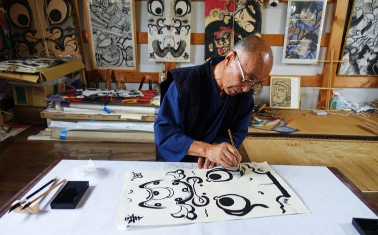 Un artisan peint les contours d'un personnage sur un cerf-volant traditionnel dans son atelier à Yuzawa, préfecture d'Akita