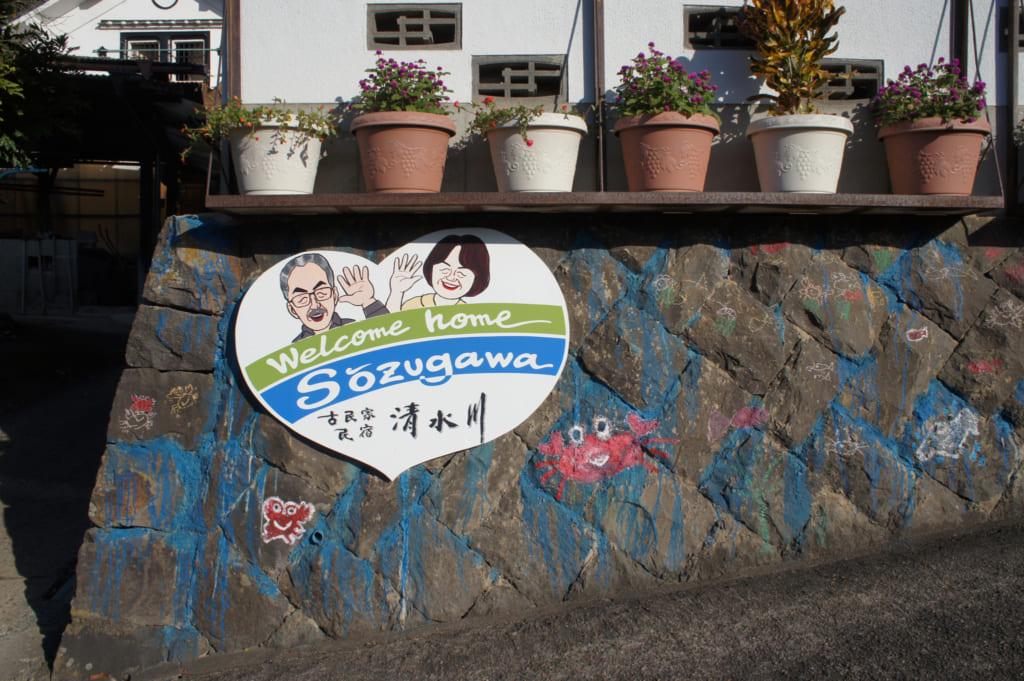 Pancarte sur laquelle une illustration montre le couple Yonemura, devant leur maison