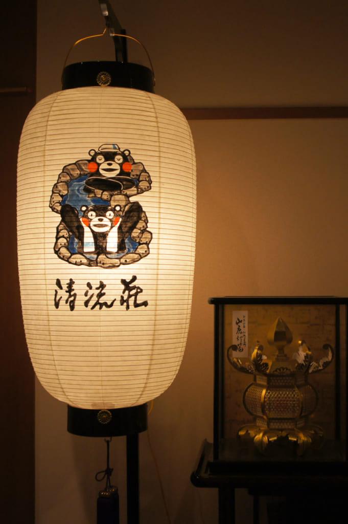 Lanterne de papier sur laquelle est peint Kumamon, à côté d'une lanterne de Yamaga
