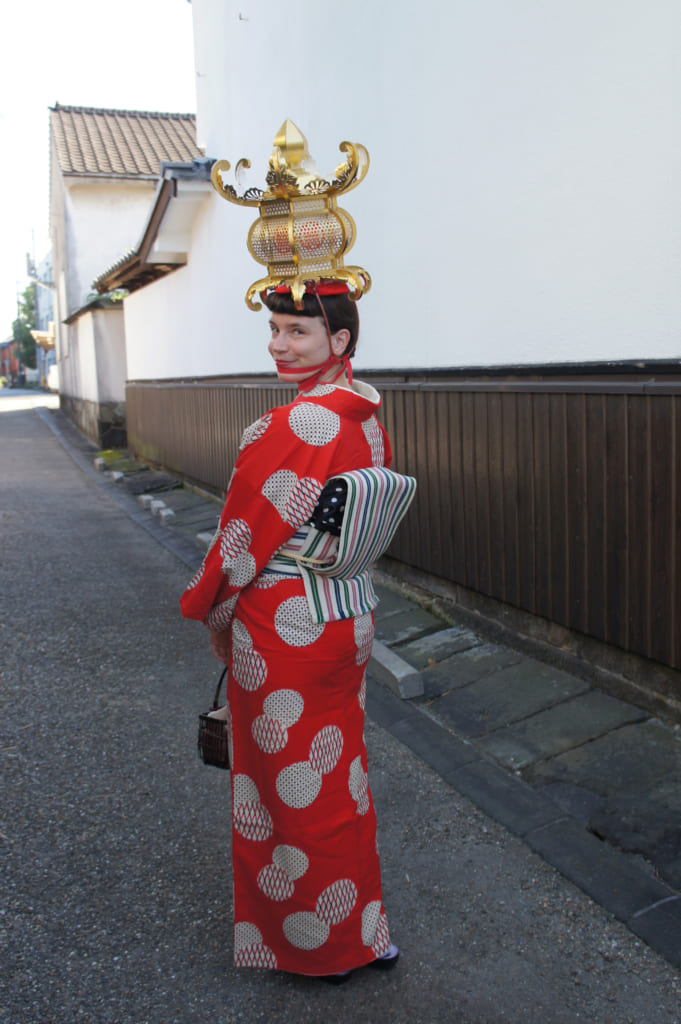 Clémentine, vêtue d'un kimono antique et portant une lanterne de papier doré sur la tête