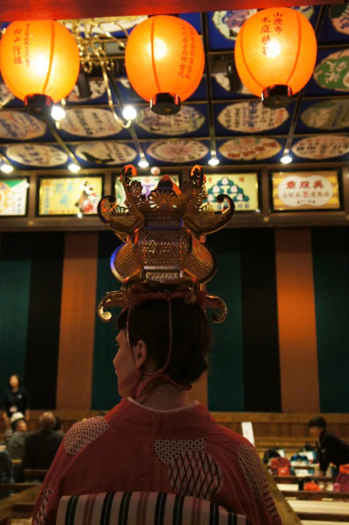 Clémetine de dos, lanterne sur la tête, dans le théâtre Yachiyo-za de Yamaga