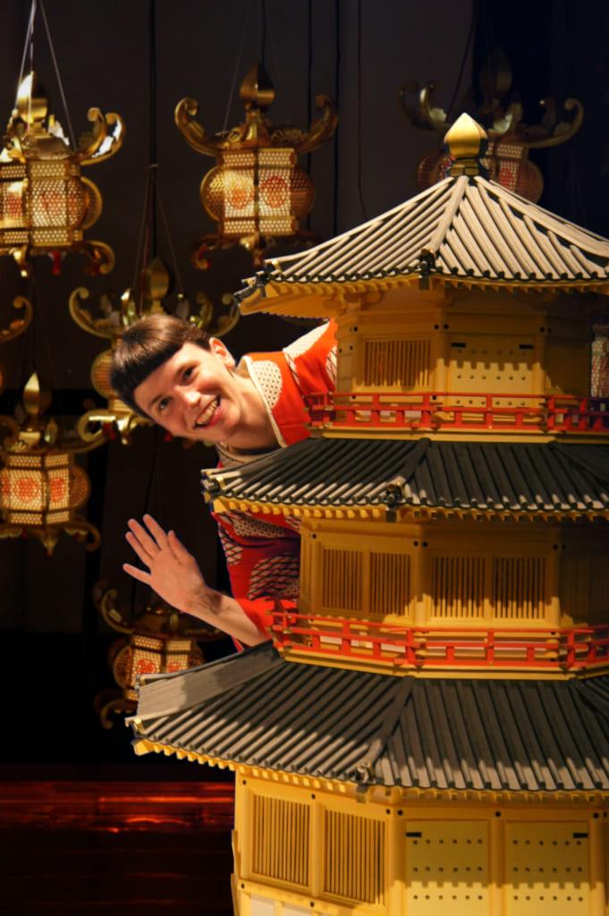 Clémentine posant à côté d'une reproduction du château de Kikuchi, fond de lanternes incrusté